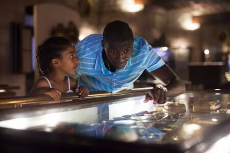 Afro father and his daughter looking at exhibits in glass stands at historical museum Stock fotó