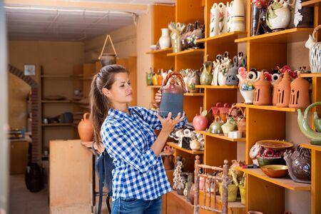 Positive young woman choosing handmade earthenware in pottery shop Foto de archivo