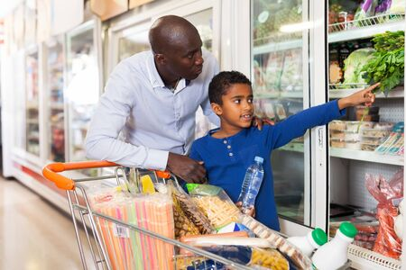 Friendly African-American family of male and tween boy making purchases in supermarket, looking for fresh vegetables Standard-Bild