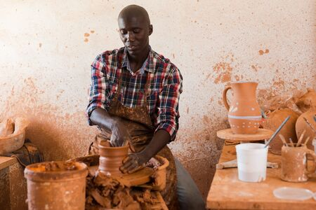 Talented young African potter at his own pottery studio working on new unique items
