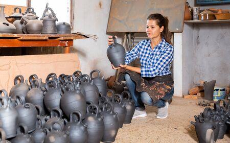 Portrait of young woman holding black ceramic jug in pottery workshop Foto de archivo