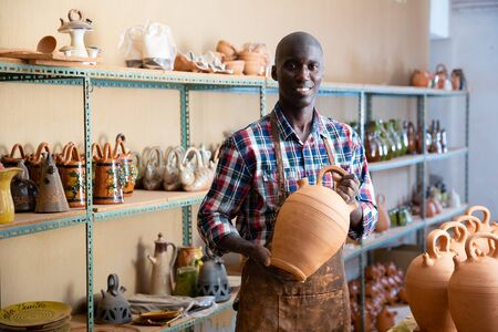 Young Afro male ceramist working in his pottery workshop