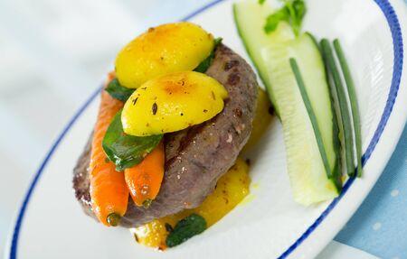 Beef patty served with baked new potatoes and carrots