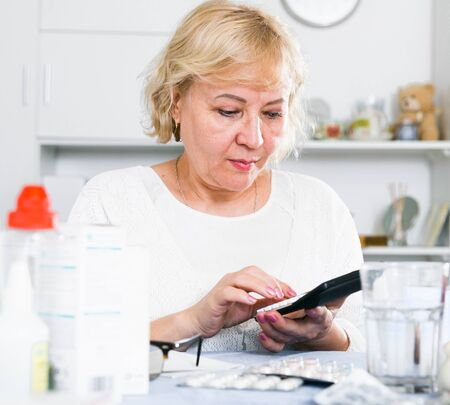 Woman looking at medicines and doctors bills sitting at table at home