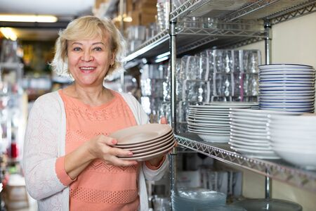 consumer woman choosing plates for kitchen in the dishes shop indoors