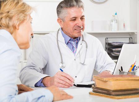 Professor of medicine training his colleague to write scientific medical research