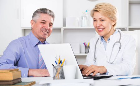 Mature man comes to doctor in clinic for advice on health Standard-Bild