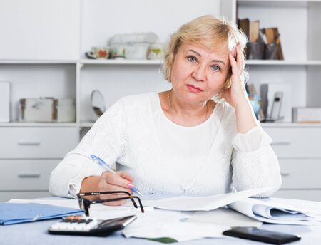 Mature woman at home is engaged in home accounting Archivio Fotografico - 129043319