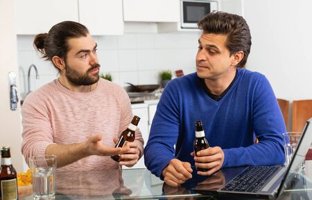 Smiling men sitting at table and drinking beer indoor Banco de Imagens