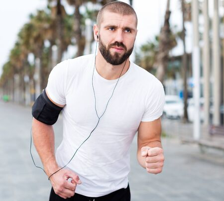 Athletic male in a white t-shirt running along the sidewalk in the city