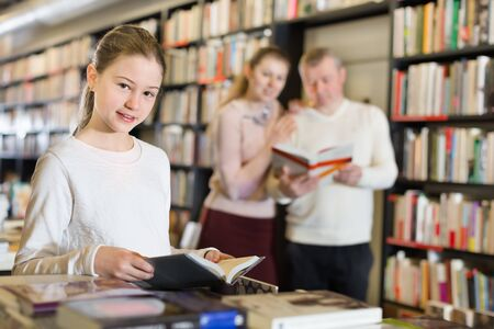 Intelligent little girl visiting bookstore with parents searching an interesting books