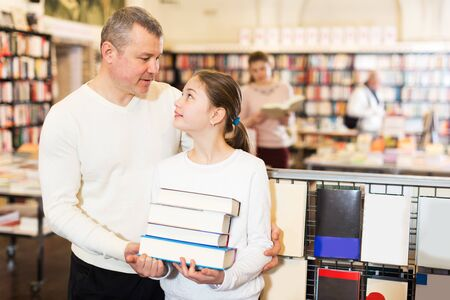 Smiling little girl with her loving father holding pile of books bought in bookstore