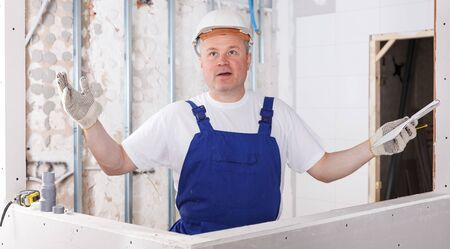 Portrait of happy male contractor inside building in process of construction