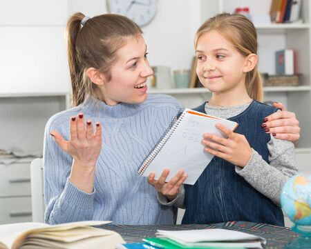 Positive young woman helping her daughter with home task