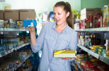 Young woman is choosing cans with tuna in shop.