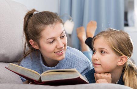 Mutter liest ein interessantes Buch für ihre Tochter