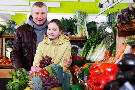 Smiling man with preteen daughter choosing pineapple during joint shopping in fruit store