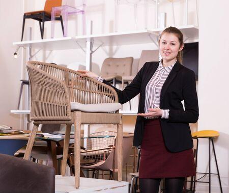 Attractive salesgirl offering original wicker loom armchair in modern furniture salon