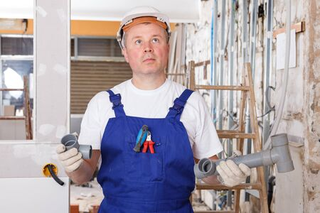 Portrait of puzzled builder holding plastic pipes elements at indoors building site 版權商用圖片 - 129091387