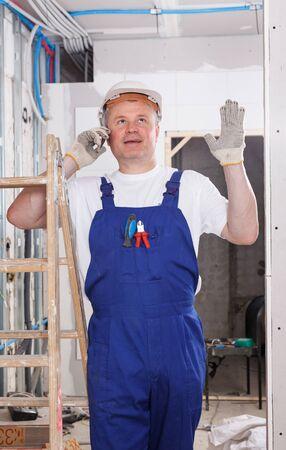 Smiling workman having phone conversation during break in work at indoors building site