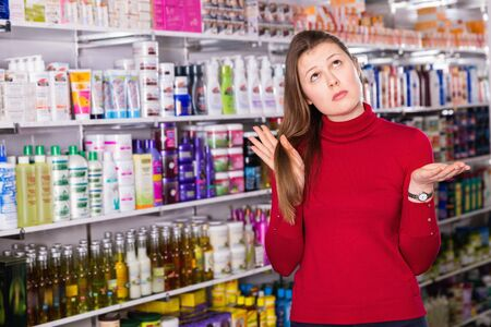 Portrait of upset unhappy  woman who is dissatisfied of quality her hair in the store.