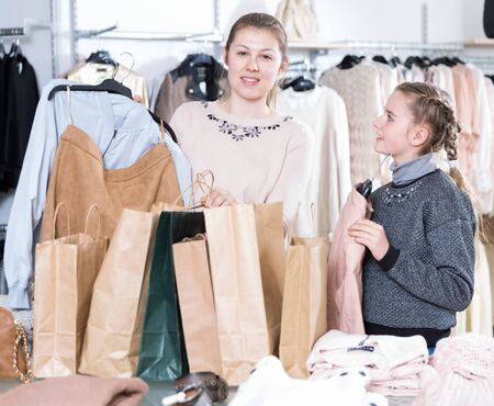 Young woman and her teen daughter looking happy with purchases in modern clothing shop 写真素材