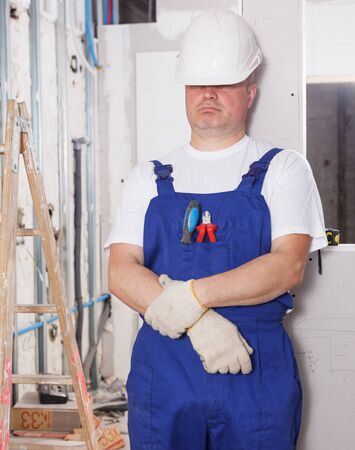 Portrait of tired male builder leaning on wall in repairable room Zdjęcie Seryjne