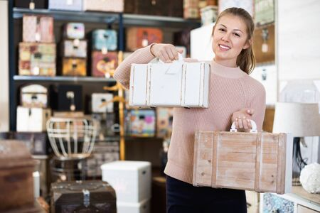 Smiling   happy positive  woman buyer holding wooden suitcase in furniture shopping room