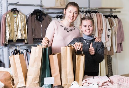 Happy young woman with daughter delighted with shopping in clothing store holding many bags