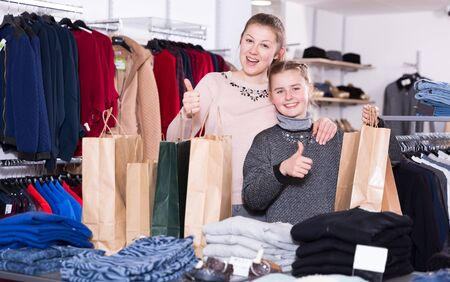 Excited mother and daughter holding shopping bags and showing thumbs up in clothes shop