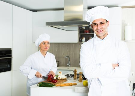 Young male chef  in white uniform standing near workplace on kitchen Stock Photo