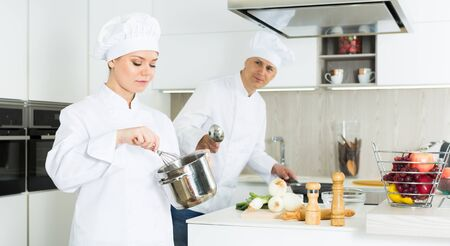 Man cook and woman standing with whisk, professional chefs in uniform working on kitchen Stock Photo