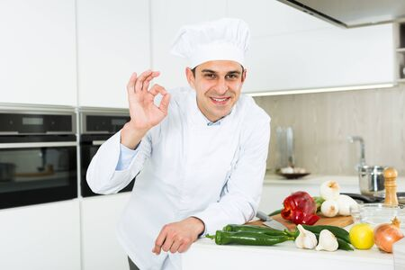 Young male cook in white uniform showing ok hand sign on kitchen Foto de archivo