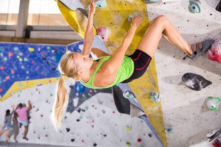 Young sporty woman training at bouldering gym without special climbing equipment Banco de Imagens - 129115022