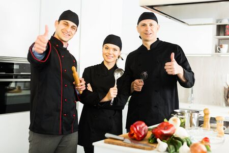 Three young cooks wearing black uniform showing thumbs up on kitchen
