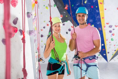 Portrait of two smiling confident athletes in mountaineering outfit ready for climbing workout at bouldering gym