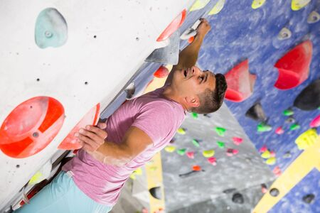 Confident male mountaineer climbing artificial rock wall without belay indoors