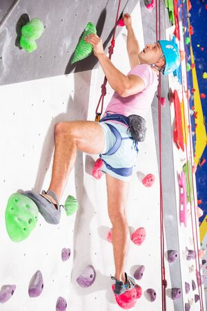 Sporty man dressed in rock climbing outfit training at a bouldering gym