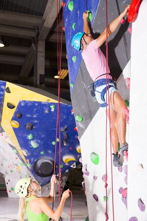 Female and male in climbing outfit training on joint workout in bouldering hall