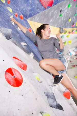 Young female alpinist practicing indoor the rock-climbing on artificial boulder without safety belts Stock Photo