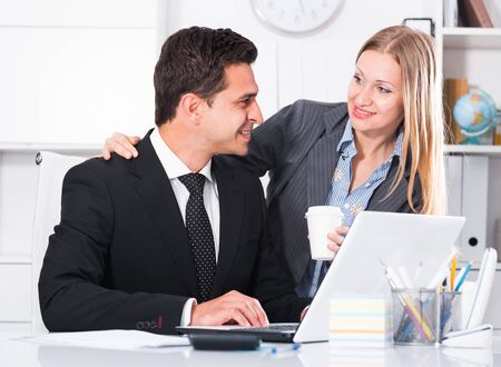 Portrait of adult business couple flirting at table at workplace in office Stock Photo