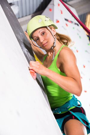 Young female alpinist practicing indoor rock-climbing on climbing wall in special equipment
