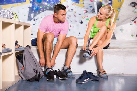 Pair of sports people dressing for mountaineering outfit for climbing on artificial rock wall indoors Stock Photo