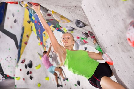 Young female alpinist practicing indoor a rock-climbing on a artificial boulder without a safety belts