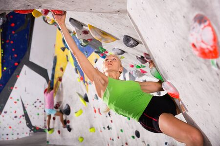 Cheerful positive sporty woman training at bouldering gym without special climbing equipment