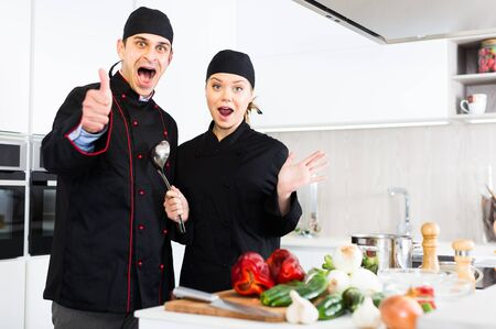 Man and woman young cooks wearing black uniform showing thumbs up on kitchen