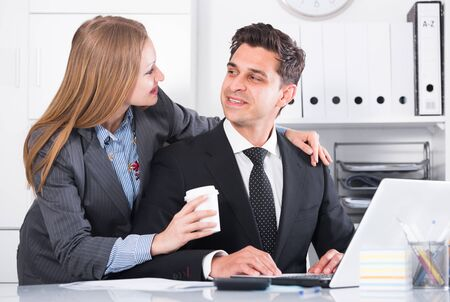 Portrait of adult business couple flirting at table at workplace in office Banque d'images - 129115180
