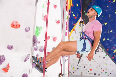 Male alpinist practicing indoor rock climbing on climbing wall in special equipment