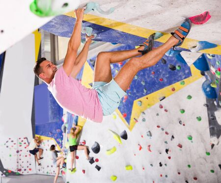 young man training at bouldering gym without special climbing equipment Stock Photo