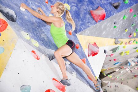 Young female alpinist practicing indoor a rock-climbing on the artificial boulder without safety belts